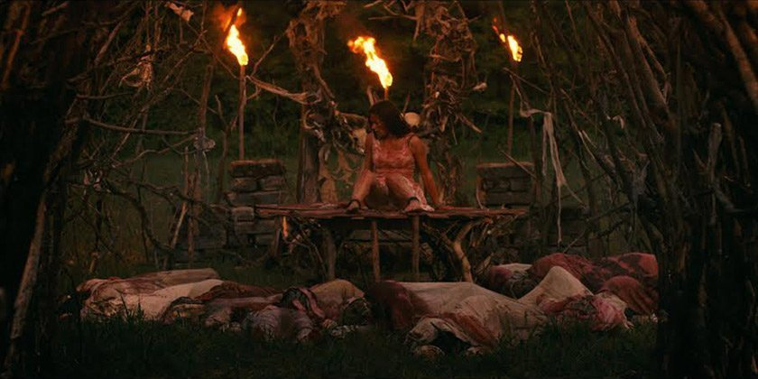 A woman on an altar in the woods surrounded by bodies