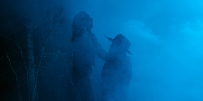 In the fog, a figure in a hat lifts and strangles another figure using one hand
